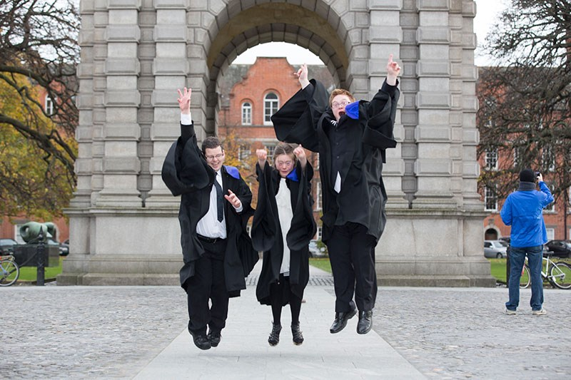 Three graduates jumping into the air in unison